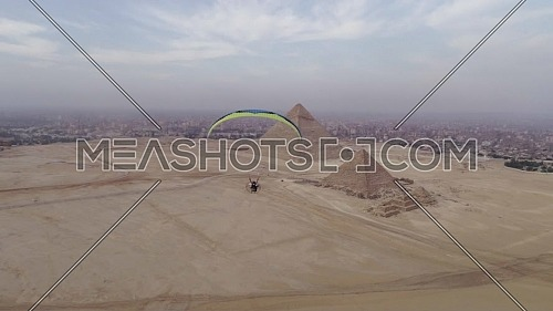 Aerial shot showing a man using power parachute flying towards The Great Pyramids of Giza in Cairo by day.
