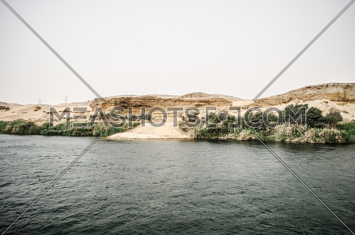 A landscape of river Nile in Egypt and sand mountains and plants