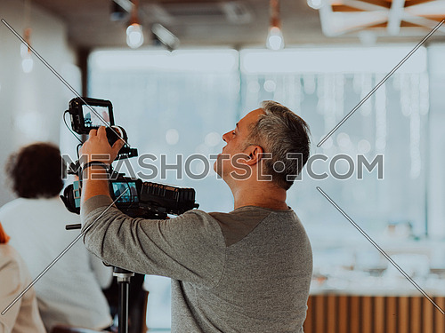 Behind the scene concept. Cameraman working on professional camera taking stock footage
