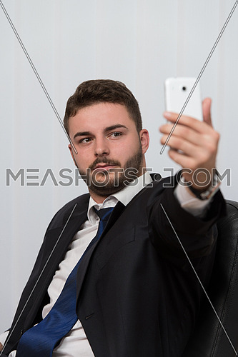 Young Businessman Working In His Office While Talking On The Phone