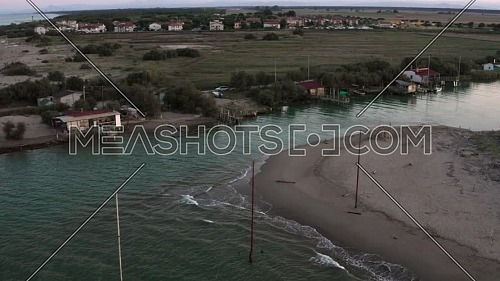 Aerial shot of the valleys near Ravenna (Fiumi Uniti) where the river flows into the sea with the typical fishermen's huts at sunset