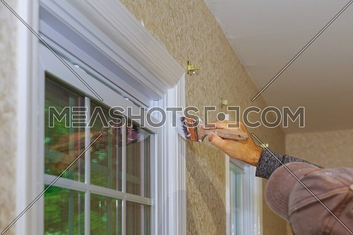 Hand with paintbrush painting a window frame trim white