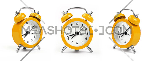 Three small yellow metal alarm clock with red bells over white background, close up, low angle view in different perspectives