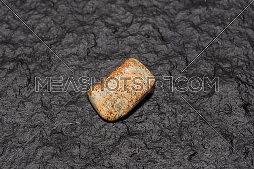Tigers eye gemstone isolated on black stone background. Macro shot