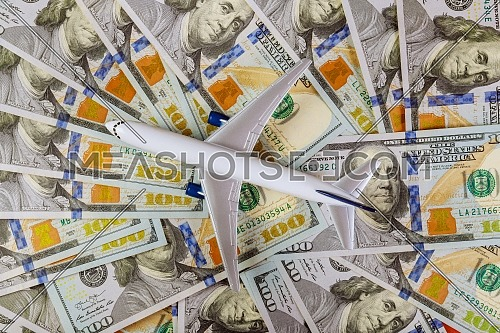 Background of one hundred dollar bills with model airplane on flat lay design to travel concept