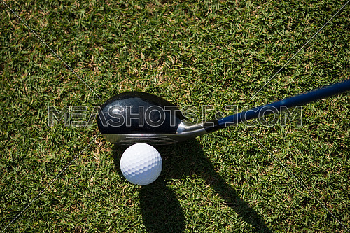 top view of golf club and ball in grass on course preparing for shot
