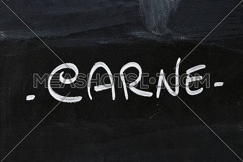 Close up white chalk CARNE word over hand written over background of black chalkboard menu
