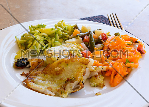In the picture a fried fish fillet with vegetables served on white dish at the restaurant.