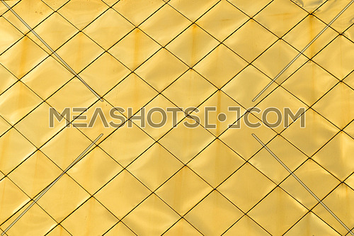 Golden metal shiny vivid rooftop tile panels texture background with highlights and reflections