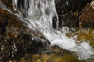 Waterfall fast stream, rapid water with drops over the rocks and stones in watercourse of river or