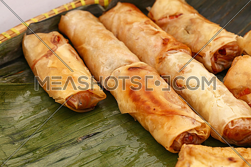 Portion of several deep fried crispy spring rolls, traditional Asian cuisine appetizer snack, served on green banana leaves, high angle view