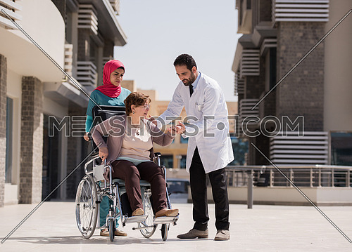 elderly sick woman in a wheelchair with medical staff in front of large modern hospital in the Middle East