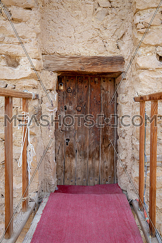 Bridge and wooden door leading to the fort of Monastery of Saint Paul the Anchorite located in the Eastern Desert, near the Red Sea mountains, Egypt