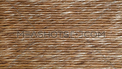 Background texture of brown natural reed or twisted straw wicker twine or packthread, detail close up