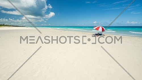 Nice beach of Varadero during a sunny day, fine white sand and turquoise and green Caribbean sea,on the right one red parasol,Cuba.concept photo,copy space.