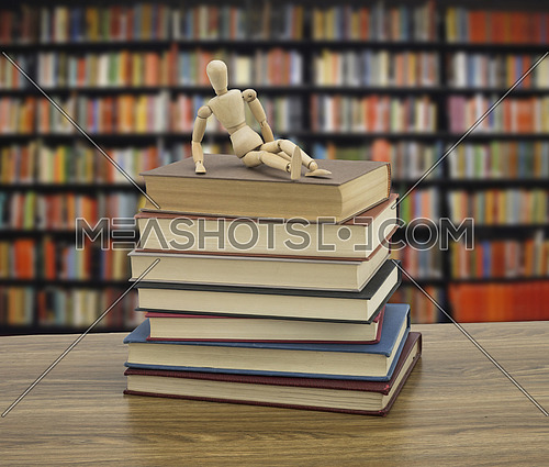 Wooden doll on some books in a library, conceptual image