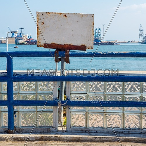 White blank grunge rusted sign attached to blue old metal fence revealing Suez Canal, Port Said, Egypt