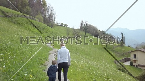 Rear view of mother and her son walking in a mountain path