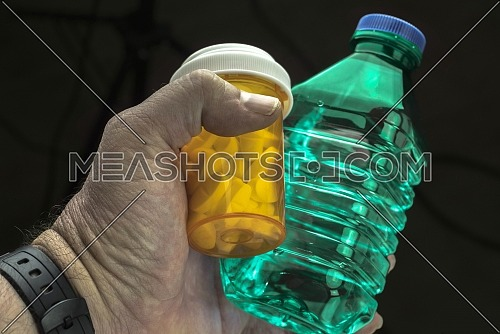 Man holds with left hand a bottle of water and a pill bottle