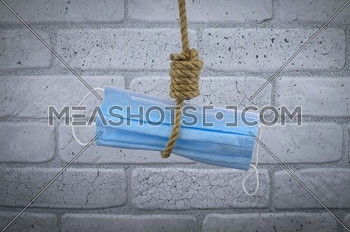 Rope noose around a protective surgical face mask, conceptual of death or mortality during the global Covid-19 or coronavirus pandemic against a brick wall background