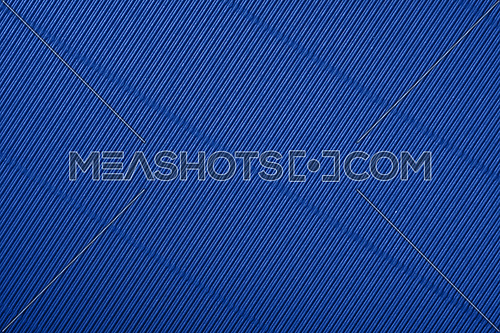 Close up diagonal background pattern texture of indigo blue corrugated packaging cardboard