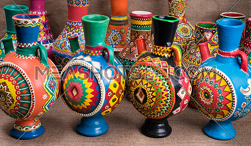 Still life of four decorated colorful handcrafted pottery jugs on sackcloth background