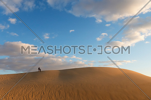 man with Sand board waking on top of high sand dunes desert in day light  with cloudy blue sky in Siwa Oasis, Egypt Adventure and Tourism wallpaper.