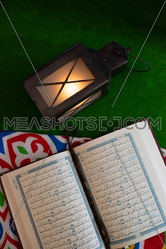 Top shot for Holly Quran Book open with Misbaha inside showing Ramadan Lantern.