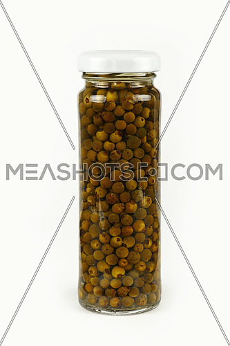 Close up of one small glass jar of pickled green hot peppercorns over white background, low angle side view