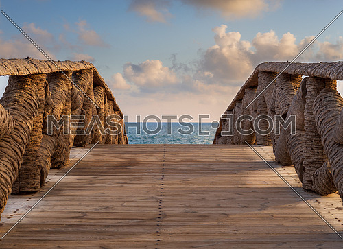 Wooden bridge made of palm trunks leading to the sea coast with partly cloudy sky in sunrise time at Montaza public park in summer time, Alexandria, Egypt