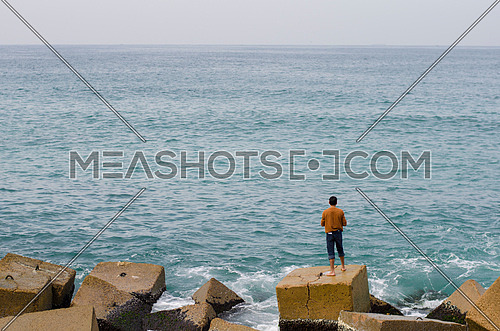 a man sitting alone on a rock by the Mediterranean sea in alexandria