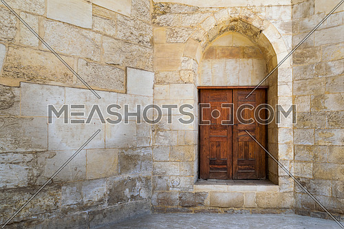 Vaulted closed decorated wooden grunge door in bricks stone wall at public historic Amir Aqsunqur Mosque, Blue Mosque, Cairo, Egypt