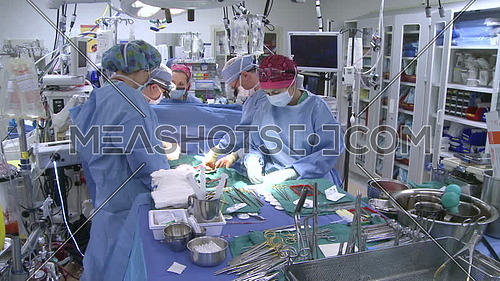 Pan left long shot of operating room while medical team performing surgery