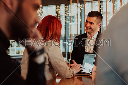 Group of friends hanging out in a coffee shop with a laptop amongst them. Happy young people sitting at restaurant using laptop computer.