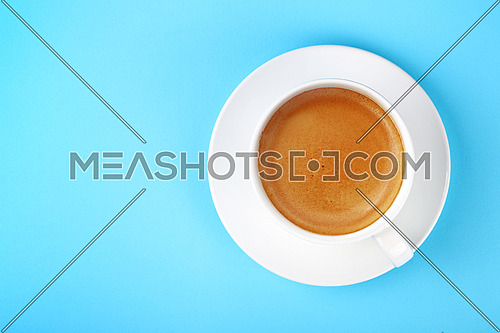 Close up one full white cup of espresso coffee and saucer over pastel blue paper background, elevated top view, directly above