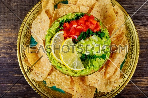 Mexican nacho chips and guacamole, yellow corn tortilla chips and a bowl of spicy on wooden background