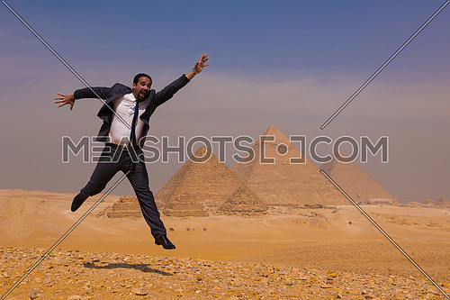 arabian business man jumping in desert with pyramids in background