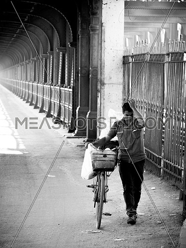 Vintage Cairo  Black & white photoset from the bridge of Imbaba; that was built in 1912 & 1924 in Egypt. A Man walking and dragging his bike.
