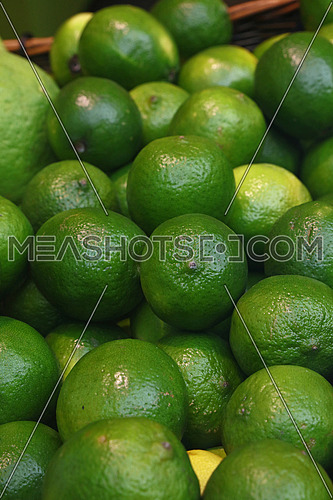 Heap of fresh green ripe lime fruits on retail market stall display, close up, high angle view