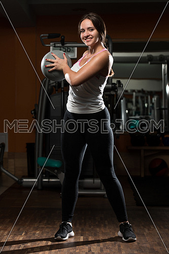 Young Woman Exercise With Medical Ball In Fitness Club