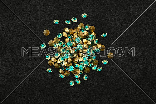 Close up heap of teal blue rhinestone crystals over black leather background, elevated top view, directly above