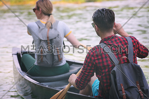 Couple adventurous explorer friends are canoeing in a wild river surrounded by the  beautiful nature