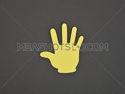 Paper made yellow STOP or HI hand gesture sticker over grey background