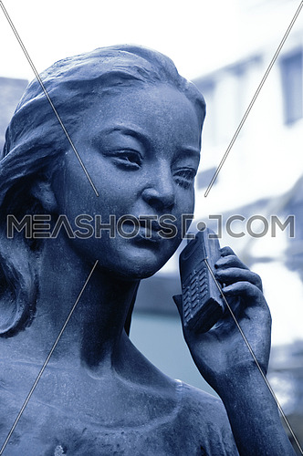 bronze statue talking at the mobile phone