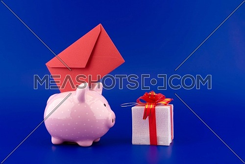 Festive red envelope being inserted into a pink piggy bank next to a present box over blue background with copy space