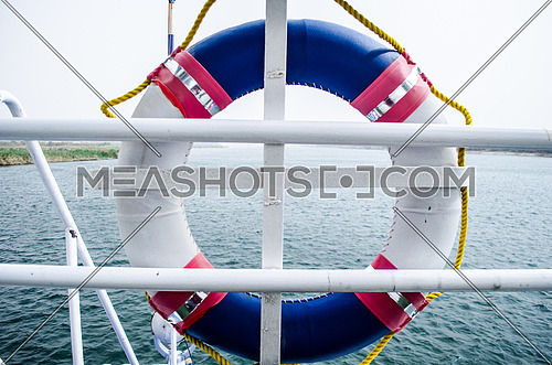 close up on a life buoy on a ship in blue, white and red straps