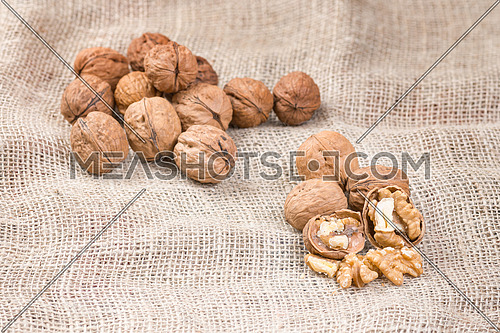 Walnut kernels and whole walnuts on rustic sack.