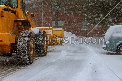 The bulldozer cleans the snow on the streets after a blizzard