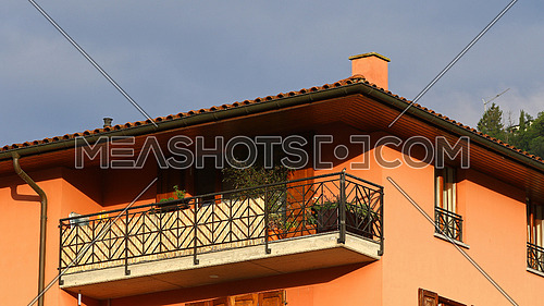New apartment building detail with roof, ceramic tiles, chimney, balcony, windows, gutter and blue skies