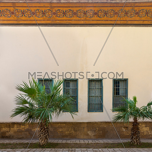 Two small palm trees and tiled stone floor in front of beige wall with orange colorful cornice decorated with floral patterns and four green window shutters